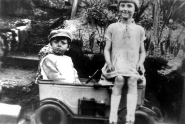 Sid aged 3 or 4 in his peddle car and his sister Eve, aged 5 or 6.