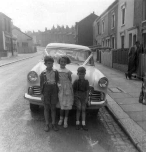 Wynne Handley (nee Winifred English) with 2 cousins and uncle Jim's taxi car Maxey Road late 1950's